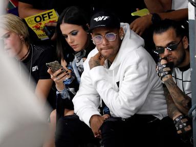 Pemain Paris Saint-Germain, Neymar dan Dani Alves menghadiri acara peragaan busana Off-White Spring-Summer 2019 Ready-to-Wear selama Paris Fashion Week, Prancis (27/9). Neymar dan Dani Alves tampil modis di acara tersebut. (AFP Photo/Francois Guillot)