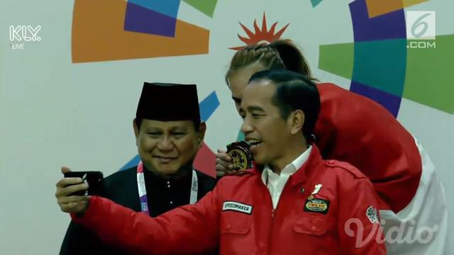 Presiden Joko Widodo mengajak Prabowo Subianto dan pesilat peraih medali emas Wewey Wita nge-vlog momen pengalungan medali emas Asian Games 2018.
