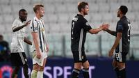 Pemain Olympique Lyon, Kenny Tete dan Joachim Andersen, merayakan kemenangan agregat dari Juventus pada laga leg kedua Liga Champions 2019/2020 di Stadion Allianz, Sabtu (8/8/2020) dini hari WIB. Juventus kalah agregat 2-2 atas Olympique Lyon. (AFP/Miguel Medina)