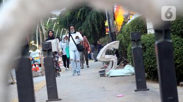 Pejalan kaki melintas di trotoar di kawasan Jalan Cikini Raya, Jakarta, Minggu (8/12/2019). Sebagai bagian dari proyek revitalisasi, kini sepanjang trotoar Cikini Raya mulai terpasang bangku-bangku taman. (Liputan6.com/Helmi Fithriansyah)