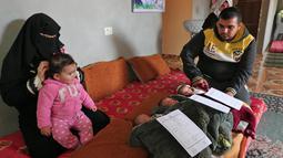 Pasangan Nidal dan Islam Al-Saiqli berpose dengan bayi kembar mereka, Jerusalem, Capital dan Palestine di Khan Yunis, Jalur Gaza, Jumat (2/2). Nama unik itu untuk memprotes Donald Trump yang mengklaim Yerusalem sebagai ibu kota Israel (SAID KHATIB/AFP)