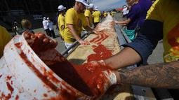 Sejumlah peserta menaburi saus tomat saat membuat pizza panjang di jalur Auto Club Speedway, di Fontana, California (10/6). Rekor baru ini mengalahkan rekor sebelumnya yang dipegang oleh peserta di Italia dengan pizza sepanjang 1,8 km. (AFP/Mark Ralston)