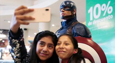 Dua penggemar wanita berselfie di dekat patung Captain America saat mengantre untuk menyaksikan pemutaran perdana film The Avengers: Endgame di La Paz, Bolivia (24/4). Film Avengers ini diputar perdana secara serentak pada 24 April 2019. (Reuters/David Mercado)