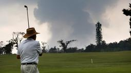 Ken McGilvray bermain golf saat kepulan asap abu vulkanik berembus dari puncak gunung Kiluaea di Volcano, Hawaii (16/5). Sekitar 2.000 orang telah dievakuasi dari rumah mereka termasuk 300 yang tinggal di tempat penampungan. (AP Photo/Jae C. Hong)