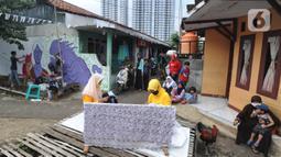 Warga menyelesaikan pembuatan batik tulis saat pelaksanaan kegiatan mural Raincity Strike #8 di Kampung Batik Cibuluh, Bogor, Minggu (22/11/2020). Kegiatan seni mural ini bertujuan diantaranya pengembangan kampung batik sebagai destinasi wisata dengan seni mural. (merdeka.com/Arie Basuki)