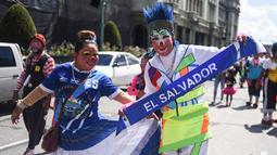 Dua badut Salvador berpose selama parade pada Konvensi Badut Regional ke-5 di kota Guatemala, Rabu (19/9). Dalam acara tersebut, dengan kostum warna-warninya mereka berparade menelusuri jalanan pusat sejarah Guatemala City. (AFP / Johan ORDONEZ)