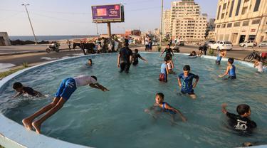 Anak-anak Palestina bermain di air mancur umum selama hari musim panas di Kota Gaza (20/7/2020). Musim panas yang terjadi di Palestina membuat anak-anak memenuhi air mancur. Mereka berupaya mendinginkan tubuh mereka dengan cara berenang di air mancur tersebut. (AFP Photo/Mahmud Hams)