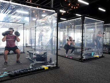 Orang-orang berolahraga dalam kotak plastik yang disediakan oleh Inspire South Bay Fitness di Redondo Beach, California pada 15 Juni 2020. Ruangan gym dengan plastik sebagai pemisah itu agar pengunjung dapat tetap berolahraga sambil tetap menjaga jarak fisik. (FREDERIC J. BROWN / AFP)