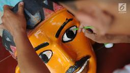 Perajin melakukan pengecatan saat membuat ondel-ondel Betawi ukuran besar di Serpong, Tangerang Selatan, Banten, Rabu (10/10). Pembuatan ondel-ondel tersebut untuk memenuhi permintaan dari wilayah Jabodetabek. (Merdeka.com/Arie Basuki)