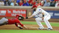 Pemain Texas Rangers, Mitch Moreland #18 dan Pemain Los Angeles, Rafael Ortega #39 oberebut pit pada inning ketujuh pertandingan Baseball di Global Life Park, Arlington, Texas. (23/5/2016). (Rick Yeatts/Getty Images/AFP)