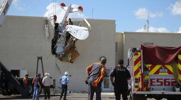Polisi dan petugas pemadam kebakaran mengevakuasi pesawat bermesin tunggal yang menabrak gedung di Bandara Regional Ak-Chin, Maricopa, Arizona, Amerika Serikat, Selasa (10/9/2019). Ercoupe 415-C mengalami kecelakaan tak lama setelah lepas landas pada Selasa pagi. (AP Photo/Ross D. Franklin)