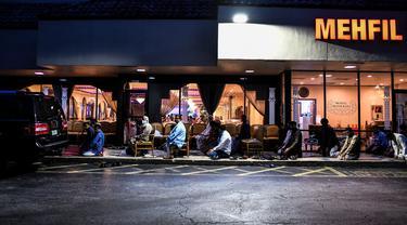 Pria Muslim melaksanakan salat di trotoar di luar restoran selama bulan suci Ramadhan di Lauderhill, Florida, Jumat (30/4/2021). Selama puasa Ramadhan, umat Islam tidak makan, minum, atau aktivitas seksual dari fajar hingga matahari terbenam. (CHANDAN KHANNA/AFP)
