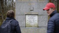 Pengunjung melihat makam filsuf ternama Jerman dan tokoh sosialisme, Karl Marx, di Pemakaman Highgate, London, Selasa (5/2). Permukaan marmer yang diambil dari makam asli Marx saat disemayamkan pada 1883 itu mengalami kerusakan parah. (Tolga AKMEN/AFP)
