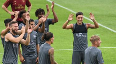 Pemain Arsenal, Mesut Ozil (kanan) menjalani sesi latihan untuk kompetisi pramusim International Champions Cup (ICC) 2018 di Singapura, Rabu (27/5). Menjelang duel kontra Atletico Madrid, Ozil dkk menikmati sesi latihan ringan. (AFP/Roslan RAHMAN)