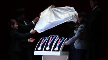 Medali Olimpiade Tokyo 2020 resmi diumumkan kepada publik saat seremoni untuk merayakan momen satu tahun jelang Olimpiade di Tokyo, Rabu (24/7/2019). Medali yang didesain Junichi Kawanishi itu berdiameter 85 mm dan dihiasi gambar dewi Yunani, Nike serta logo Olimpiade. (Behrouz MEHRI/AFP)