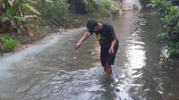 Salah satu warga ketika melihat ikan di sungai Bektiharjo Tuban mati mendadak dan mengapung