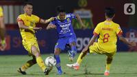 Gelandang Persib, Febri Hariyadi (tengah) mencoba lolos dari adangan pemain Bhayangkara FC pada lanjutan Shopee Liga 1 Indonesia di Stadion PTIK, Jakarta, Rabu (23/10/2019). Laga kedua tim berakhir imbang 0-0. (Liputan6.com/Helmi Fithriansyah)