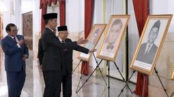 Presiden Joko Widodo (tengah) dan Wakil Presiden Ma'ruf Amin (kanan) melihat-lihat foto Pahlawan Nasional di Istana Negara, Jakarta, Jumat (8/11/2019). Jokowi menganugerahkan gelar Pahlawan Nasional kepada 6 tokoh yang dianggap berjasa untuk Indonesia. (Foto: Lukas-Biro Pers Sekretariat Presiden)