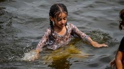 Seorang anak perempuan mendinginkan diri ke perairan Laut Arab saat musim panas di Karachi pada 5 Juli 2020. Warga Pakistan menghabiskan hari yang cerah dengan berenang di tengah pandemi virus corona. (Photo by Rizwan TABASSUM / AFP)