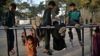 Anak-anak bermain pada palang besi yang terpasang di Shahr-e Naw Park, Kabul, Afghanistan, 9 September 2021. Taliban menguasai Afghanistan setelah pasukan Amerika Serikat meninggalkan negara tersebut. (HOSHANG HASHIMI/AFP)