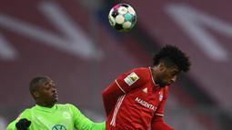 Penyerang Bayern Munchen, Kingsley Coman, berebut bola dengan bek Wolfsburg, Jerome Roussillon, pada laga lanjutan Liga Jerman di Allianz Arena, Kamis (17/12/2020) dini hari WIB. Bayern Munchen menang 2-1 atas Wolfsburg. (AFP/Christof Stache/pool)