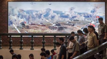 Foto yang diambil 24 Juli 2017. Pengunjung melintas di depan lukisan yang menunjukkan sejumlah tank saat berperang di Sinchon Museum of American War Atrocities, Sinchon, Pyongyang. Museum ini didedikasikan kepada Pembantaian Sinchon. (AFP Photo/Ed Jones)