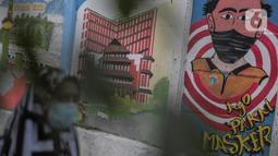 Warga saat melintasi mural bertuliskan protokol kesehatan COVID-19 di Kawasan Kota Bambu, Jakarta, Selasa (20/10/2020). Sehingga total kasus Covid-19 di Indonesia menjadi 373.109 kasus dengan DKI Jakarta tetap menduduki peringkat pertama dengan 1.000 kasus. (Liputan6.com/Johan Tallo)
