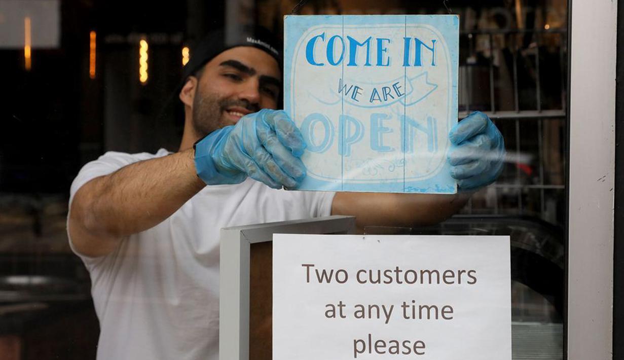 Pemilik kedai kopi memasang pengumuman di tokonya, London, Inggris, Minggu (17/5/2020). Beberapa restoran, kafe, dan toko katering di Inggris secara bertahap kembali buka setelah pemerintah melonggarkan kebijakan lockdown akibat virus corona COVID-19. (Xinhua/Tim Ireland)