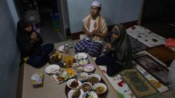 Sebuah keluarga Muslim Thailand berdoa sebelum berbuka puasa di ruang tamu rumah mereka di Bangkok, pada 28 April 2020. Banyak tempat ibadah ditutup guna membendung penyebaran Virus Corona COVID-19 ketika Umat Muslim di seluruh dunia menyambut bulan suci Ramadan. (AP Photo/Gemunu Amarasinghe)