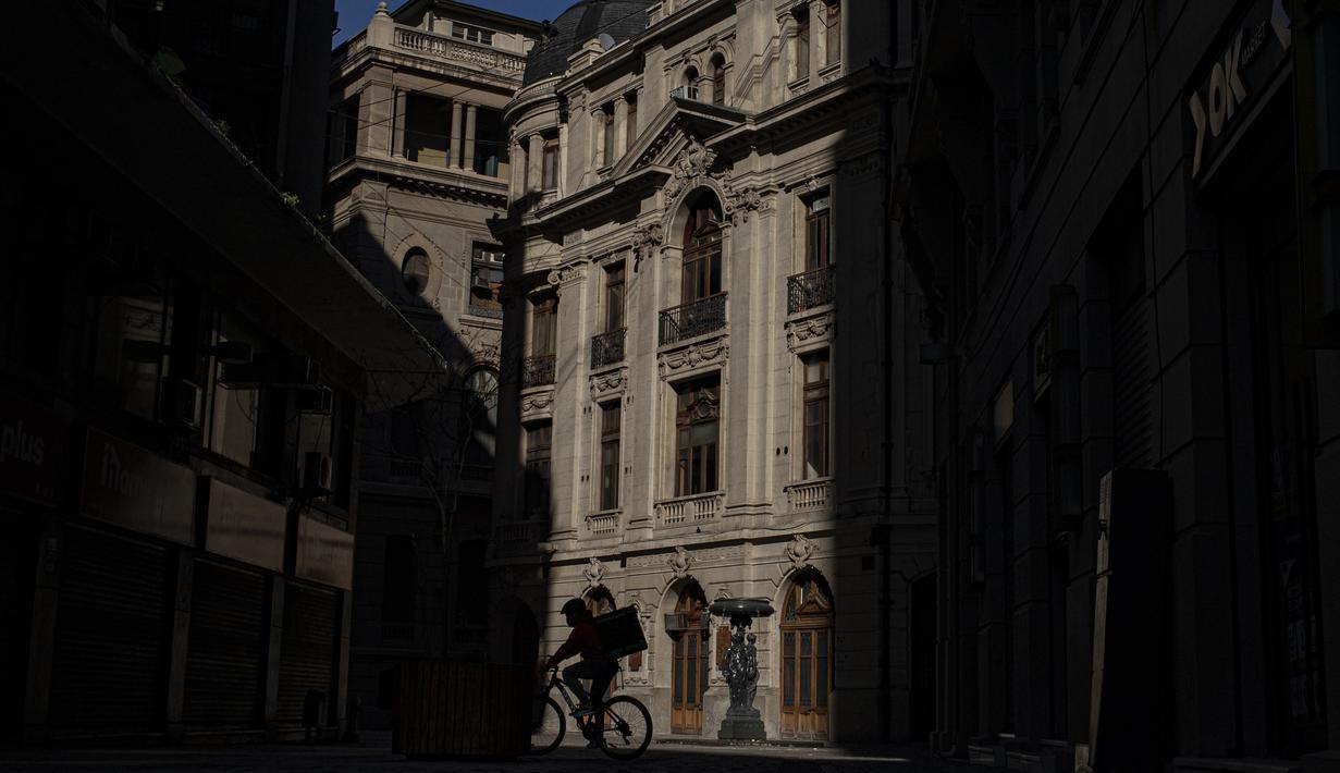 Seorang pesepeda yang mengantarkan makanan melewati jalan sepi di pusat kota Santiago, Chile, Sabtu (12/6/2021). Ibu kota Chile telah mengembalikan tindakan karantina di tengah meningkatnya kasus COVID-19, meskipun hampir 60% warga negara itu sudah divaksinasi sepenuhnya. (AP Photo/Esteban Felix)