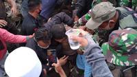 Tim gabungan yang bertugas menyelamatkan  dua petugas kemanan yang terjebat diantara puing-puing reruntuhan kantor Gubernur Sulbar berhasil mengevakuasi mereka dalam keadaan hidup. (Liputan6.com/Abdul Rajab Umar)