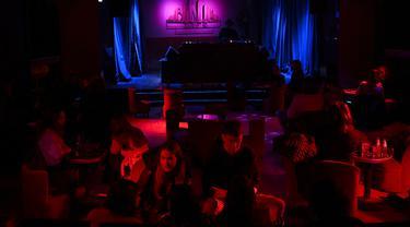 Kaum muda menikmati malam di Kafe Berlin di Madrid (17/1/2021). Dengan infeksi virus Corona harian mencapai rekor tertinggi setelah liburan Natal, beberapa wilayah Spanyol bergerak untuk semakin memperketat pembatasan pada kehidupan sosial. (AFP/Gabriel Bouys)