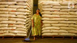 Pekerja tersenyum di samping karung beras Bulog di Kelapa Gading, Jakarta, Kamis (27/2/2020). Jelang Ramadan dan Idul Fitri 2020 Perusahaan Umum Badan Urusan Logistik atau Perum Bulog siap mengamankan pasokan beras di seluruh wilayah Indonesia mencapai 1,7 juta ton. (merdeka.com/Imam Buhori)