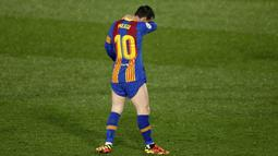 Striker Barcelona, Lionel Messi, tertunduk lesu usai ditaklukkan Real Madrid pada laga Liga Spanyol di Stadion Alfredo di Stefano, Minggu (11/4/2021). Real Madrid menang dengan skor 2-1. (AP/Manu Fernandez)