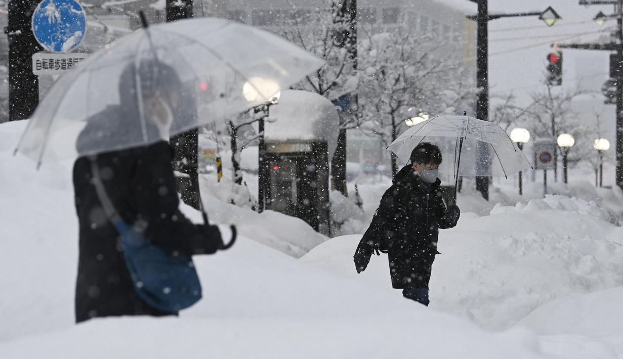 Orang-orang berjalan di atas salju yang menumpuk di depan stasiun kereta Toyama di Toyama, di pantai Laut Jepang, Senin (11/1/2021). Badai musim dingin yang dahsyat menghantam kawasan pesisir di sepanjang Laut Jepang. (Kyodo News via AP)