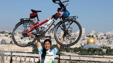 Pria Taiwan, Jacky Chen (40), berpose mengangkat sepedanya di Bukit Zaitun yang menghadap ke Kota Tua Yerusalem dan Kubah Batu pada 10 Juni 2019. Mantan teknisi elektronik itu berhenti dari pekerjaannya demi mewujudkan impiannya berkeliling dunia dengan sepeda. (MENAHEM KAHANA/AFP)