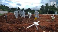 Petugas melakukan pemakaman korban COVID-19 di TPU Jombang, Tangerang Selatan, Banten, Senin (18/1/2021). Berdasarkan penuturan keluarga, keluarganya meninggal akibat terlambat penanganan karena rumah sakit rujukan COVID-19 penuh. (merdeka.com/Arie Basuki)