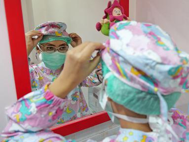 dr. J. Mila Hardiani C merapikan tutup kepala di ruang poli anak  di RSIA Tambak, Jakarta, Kamis (18/6/2020). Dokter menggunakan APD lengkap bertujuan untuk memberikan kenyamanan kepada anak-anak yang menjalani pemeriksaan juga guna mengantisipasi penularan COVID-19. (Liputan6.com/Herman Zakharia)