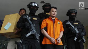 Tersangka pembunuh satu keluarga di Bekasi Haris Simamora (tengah) mendapat pengawalan polisi bersenjata di Polda Metro Jaya, Jakarta, Kamis (21/2). Polda Metro Jaya melimpahkan berkas perkara kasus Haris ke Kejari Bekasi. (Merdeka.com/Imam Buhori)