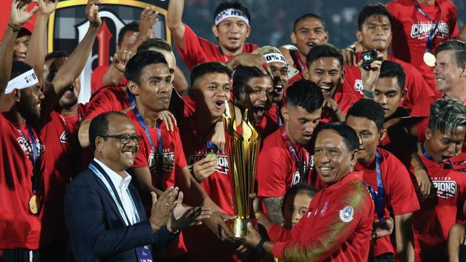 Kapten Bali United, Fadhil Sausu, menerima trofi gelar juara Liga 1 2019 di Stadion Kapten I Wayan Dipta, Bali, Minggu (22/12). Bali berada di peringkat satu dengan meraih 64 poin. (Bola.com/Aditya Wany)