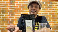 Pemilik kedai Kopilink, Takdir Hamzah yang memperlihatkan biji kopi Sota Merauke. (Foto: Liputan6.com / KabarPapua.co / Abdel Syah)