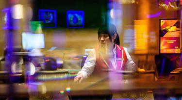 Anggota staf mempersiapkan meja kasino di resor MGM Cotai di Macau (13/2). MGM China membuka resor mega multi-miliar dolar baru di strip Cotai yang mewah di Macau pada tanggal 13 Februari. (AFP Photo/Anthony Wallace)