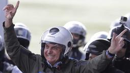 Presiden Brasil Jair Bolsonaro melambaikan tangan sebelum melakukan tur sepeda motor dengan para pendukung di Brasilia, pada Minggu (9/5/2021). Bolsonaro memimpin ratusan pengendara motor melakukan perjalanan mengelilingi ibu kota Brasil untuk memperingati Hari Ibu. (AP Photo/Eraldo Peres)
