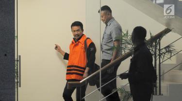 Bupati Jombang Nyono Suharli Wihandoko dikawal petugas berjalan keluar usai menjalani pemeriksaan perdana di Gedung KPK, Jakarta, Rabu (7/2). Nyono diperiksa sebagai tersangka dalam Operasi Tangkap Tangan (OTT) KPK. (Liputan6.com/Herman Zakharia)