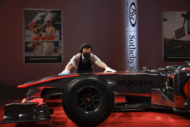 Seorang staf memoles mobil McLaren MP4-25A Mercedes yang dikendarai Lewis Hamilton pada GP Turki 2010, di Sotheby London, Selasa (18/5/2021). Mobil McLaren tersebut  akan dilelang di Grand Prix (GP) Inggris pada bulan Juli 2021 mendatang. (AP Photo/Alberto Pezzali)