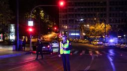 Petugas kepolisian menunggu untuk memeriksa dokumen pengemudi di Athena, Yunani, Minggu (25/10/2020). Pemerintah Yunani telah memberlakukan jam malam di Athena, Thessaloniki, dan daerah lain dengan tingkat infeksi COVID-19 yang tinggi serta kewajiban penggunaan masker. (AP Photo/Yorgos Karahalis)