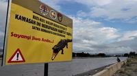 Salah satu papan informasi keberadaan buaya muara di Sungai Palu yang di pasang BKSDA Sulteng di Kelurahan Lere, Kecamatan Palu Barat pada Juni, 2020. (Foto: Liputan6.com/ Heri Susanto).