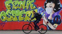 Pengendara sepeda melewati grafiti bertema virus corona COVID-19 yang bertuliskan 'Happy Easter' pada dinding di Hamm, Jerman, Senin (13/4/2020). Kasus COVID-19 tertinggi di dunia ditempati oleh Amerika Serikat, Spanyol, Italia, Prancis, Jerman, dan China. (AP Photo/Martin Meissner)