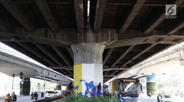 Peserta mengikuti kompetisi mural di tiang tol kawasan Rawamangun, Jakarta, Sabtu (4/5). Kompetisi tersebut digelar dalam rangka menyambut kegiatan Asian Games 2018 yang akan berlangsung di Jakarta dan Palembang. (Liputan6.com/Immanuel Antonius)