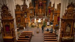 Imam Evaldas Darulis memimpin misa pada malam Natal yang disiarkan langsung dari Gereja Katolik Roma Santo Fransiskus Asisi yang kosong di Vilnius, Lithuania, Kamis (24/12/2020). Natal tahun ini dirayakan oleh umat Kristiani dunia di tengah pandemi COVID-19. (AP Photo/Mindaugas Kulbis)